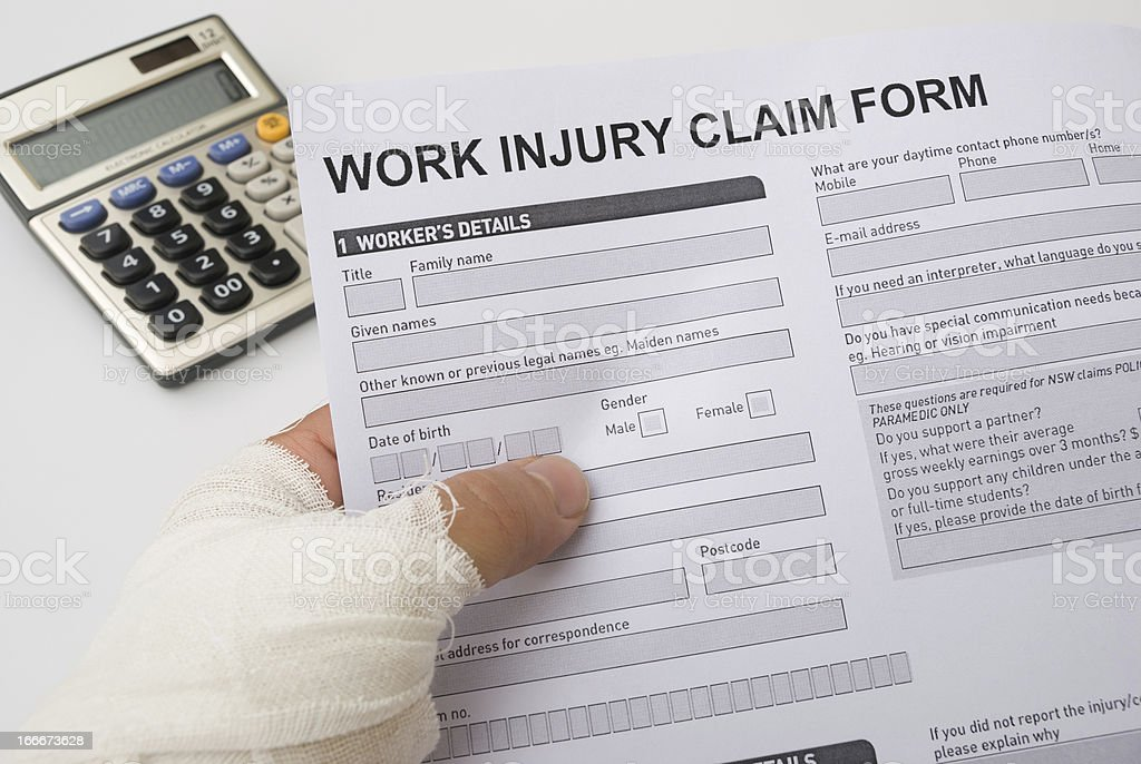 hurted hand holding a work injury claim form stock photo