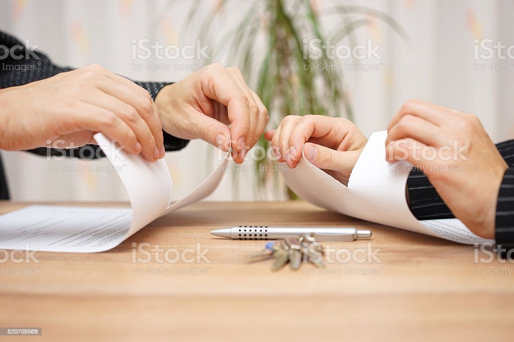 Husband and wife are tearing divorce papers stock photo