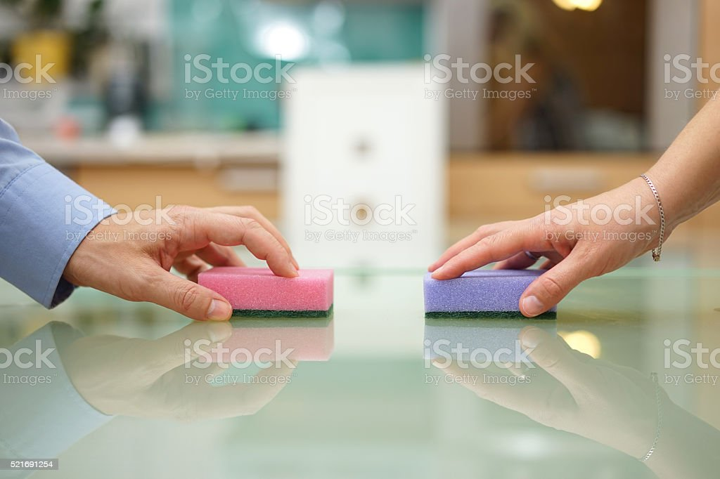 husband and wife cleaning home together stock photo