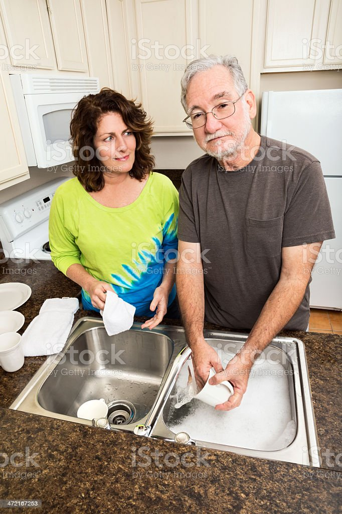 Husband and wife doing the dishes together royalty-free stock photo