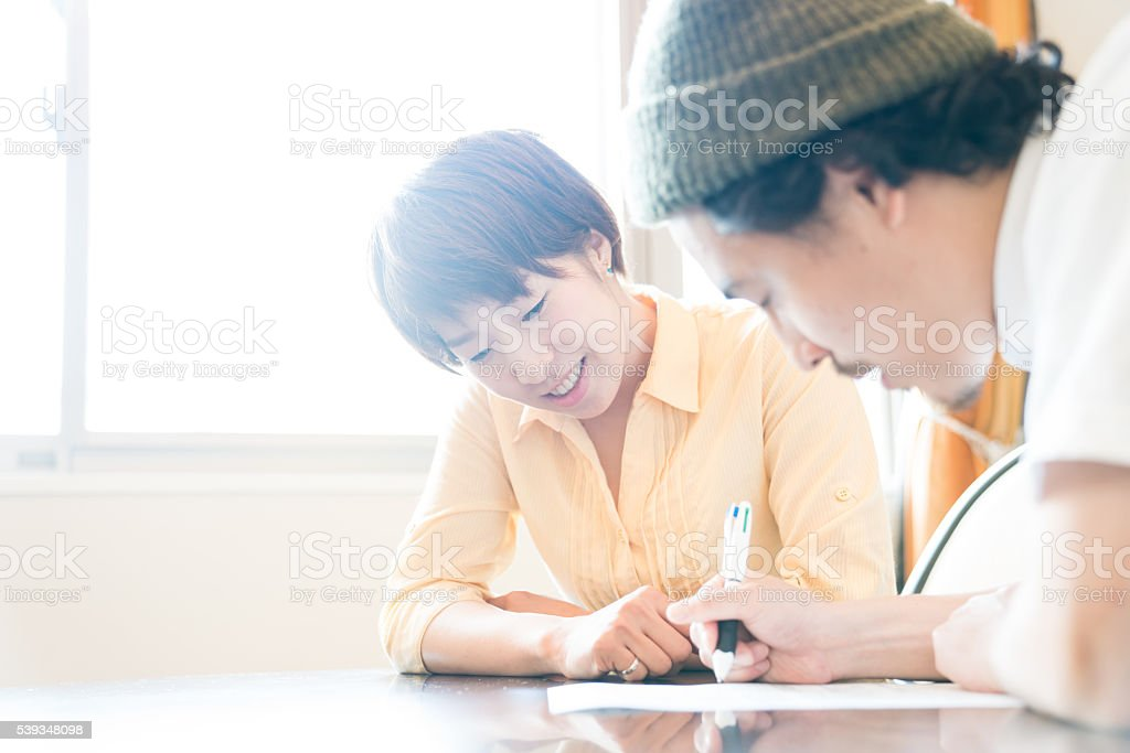 Husband and wife fill out important paperwork stock photo