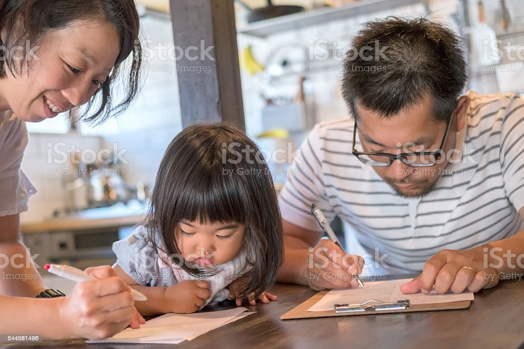 Husband and Wife Fill Out Paperwork While Young Daughter Watches stock photo