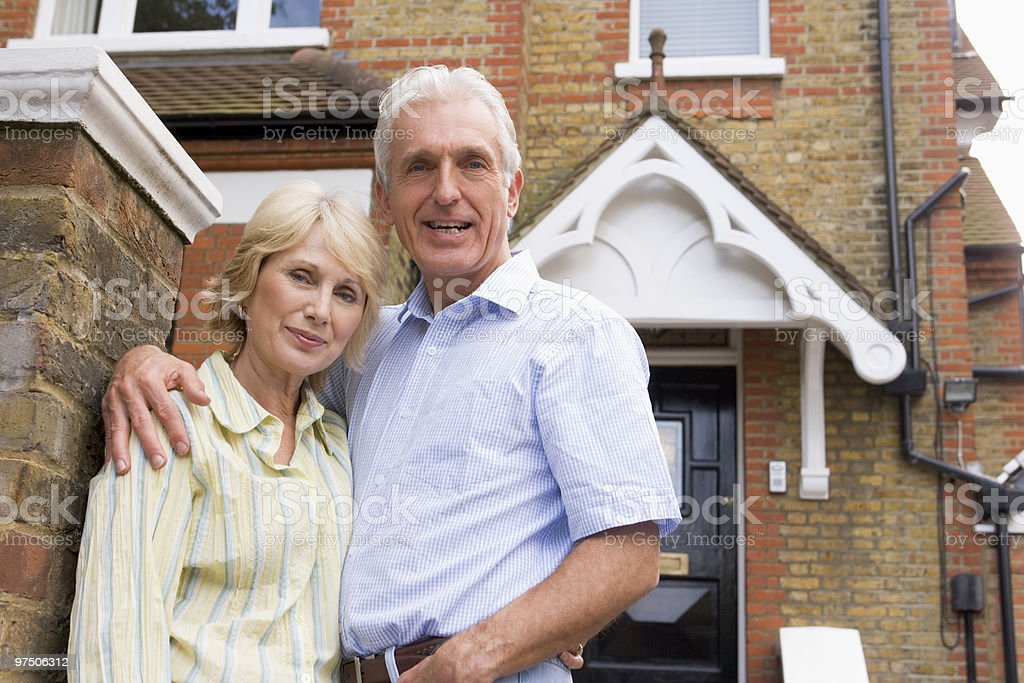 Husband and Wife Hugging Outside House stock photo