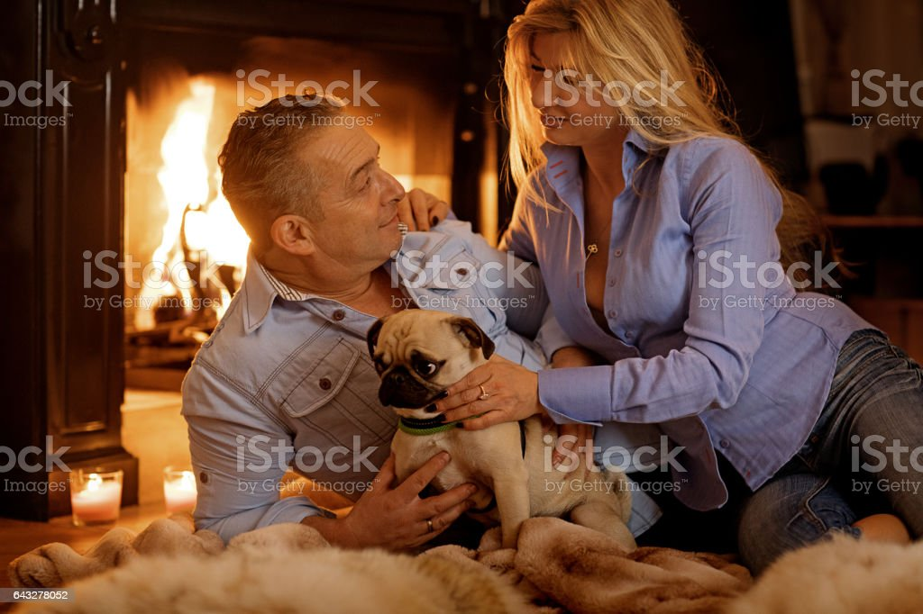 Husband and wife in christmas scene with festive decorations in indoor setting stock photo