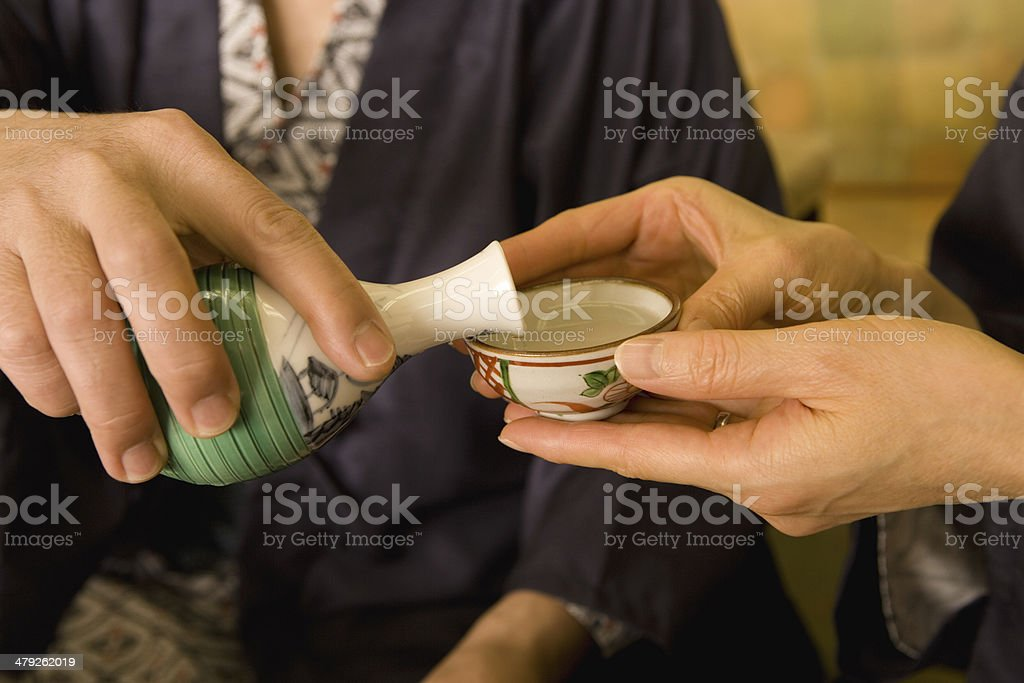Husband and wife in yukata pouring out alcohol drink stock photo