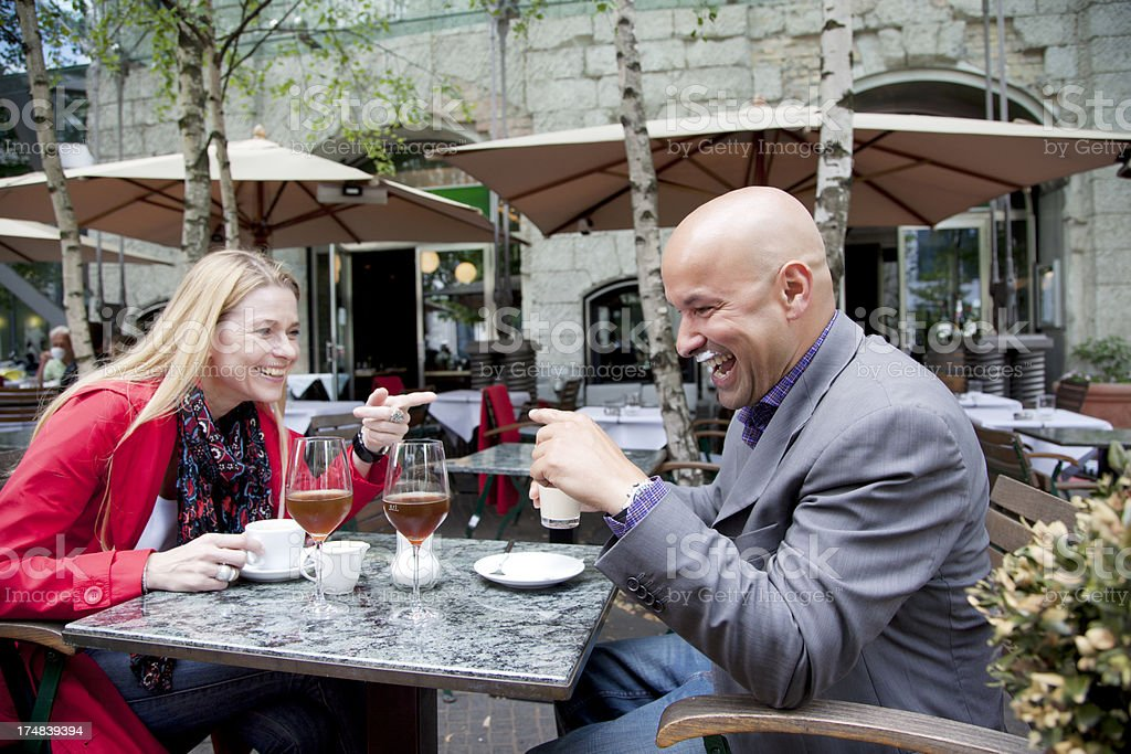 husband and wife laughing at coffee shop stock photo