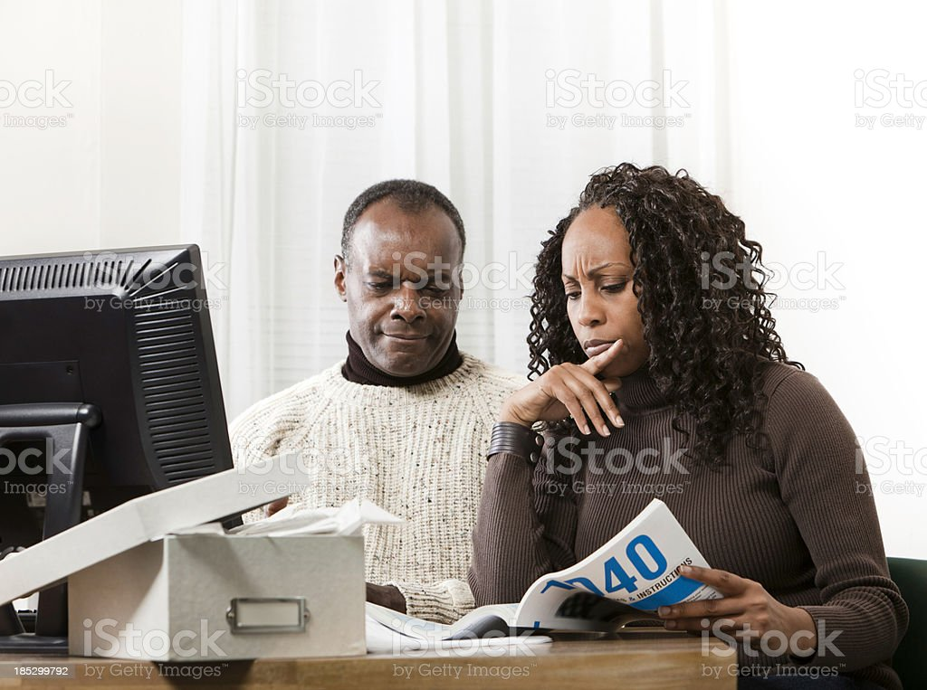 HUsband and Wife Reading Income Tax Instructions royalty-free stock photo