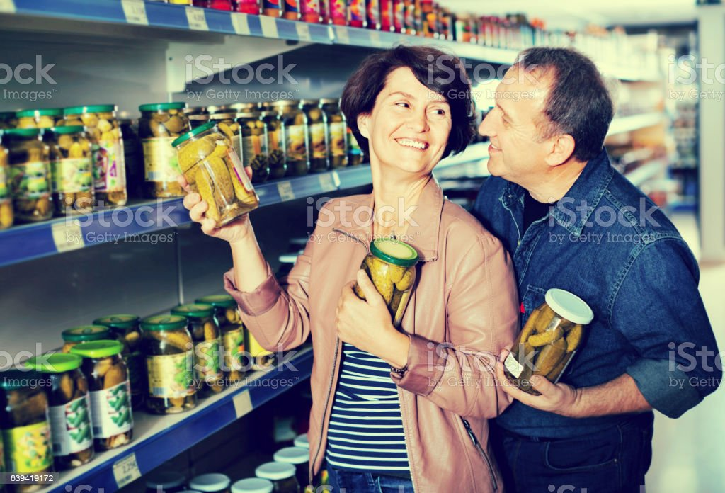 Husband and wife selecting a pickles at  store stock photo