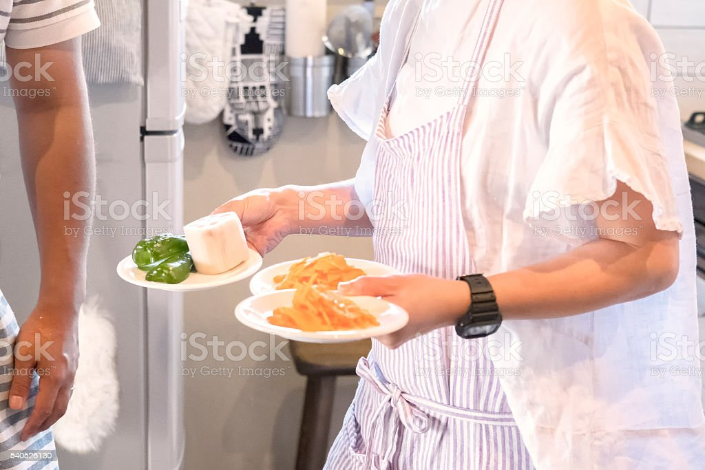 Husband and Wife Wearing Aprons Preparing Dinner in Home Kitchen stock photo