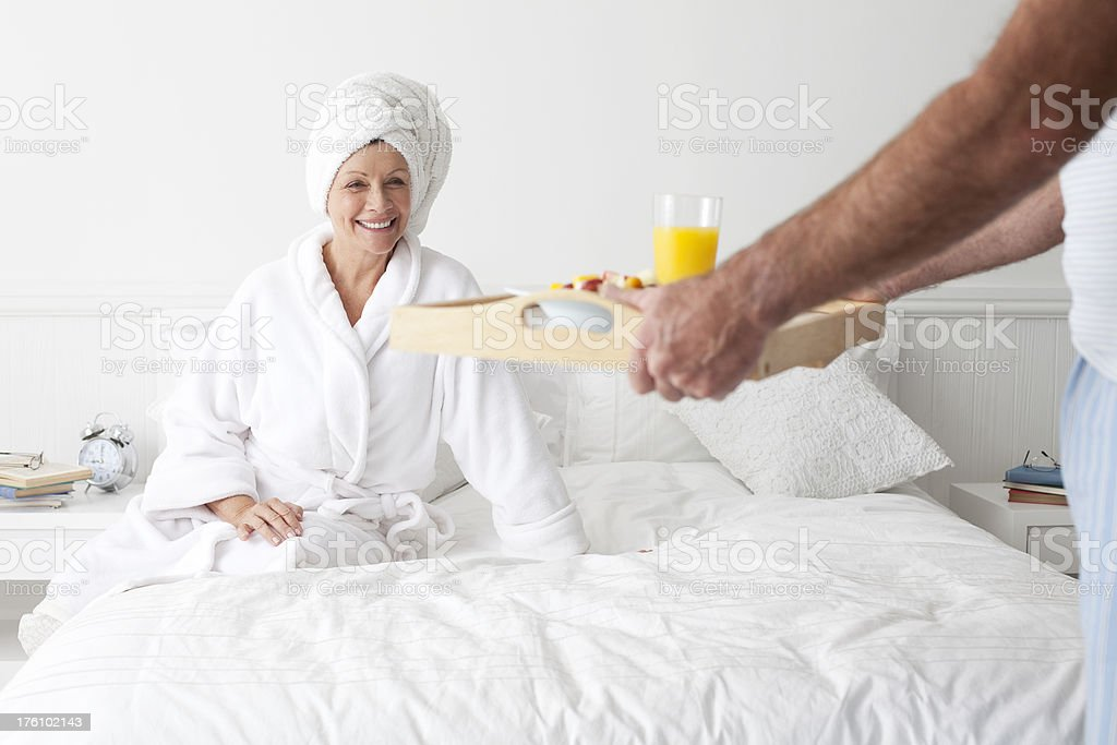 Husband brining his wife breakfast in bed. royalty-free stock photo