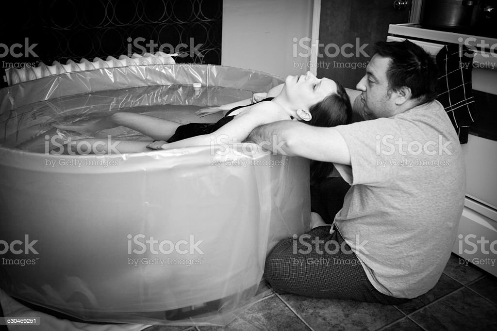 Husband Comforts Wife During Home Water Birth stock photo