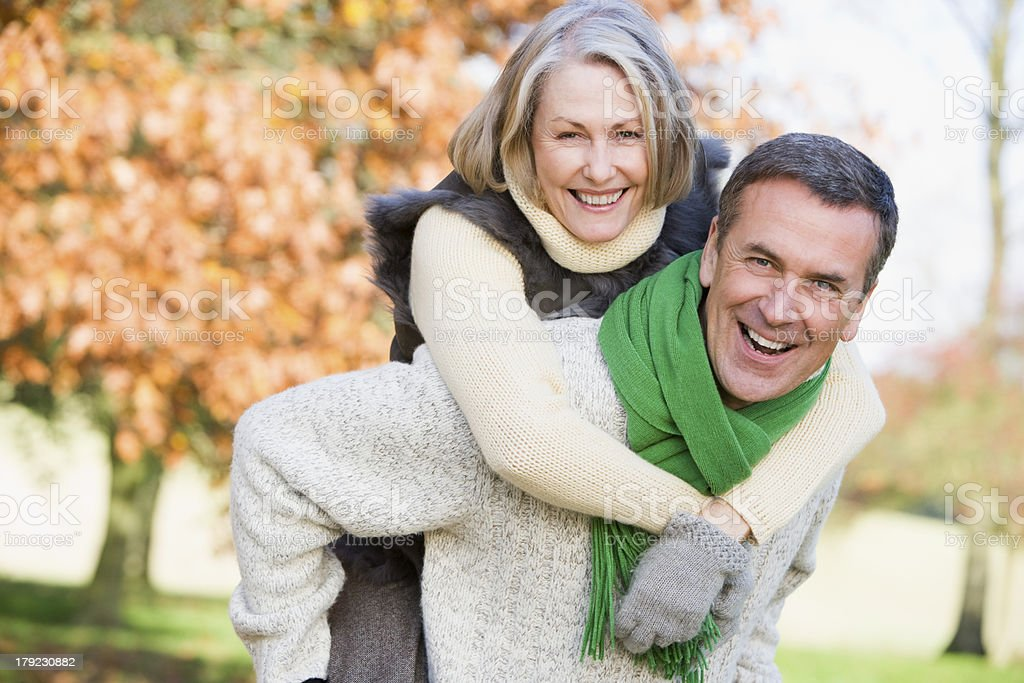 Husband giving wife piggyback ride in autumn stock photo