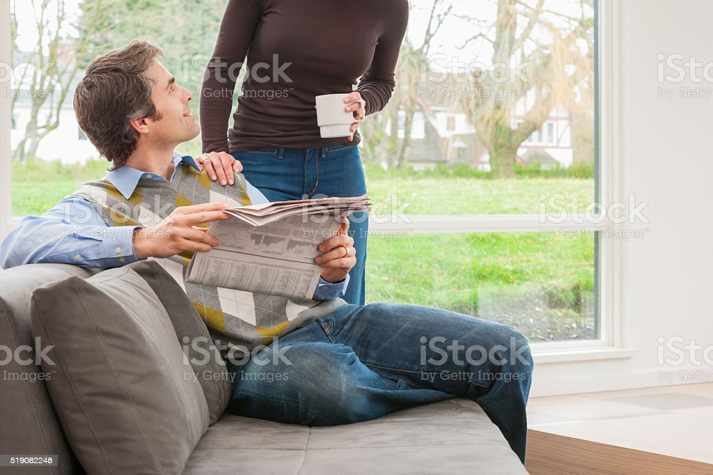 Husband holding newspaper and looking up at wife stock photo