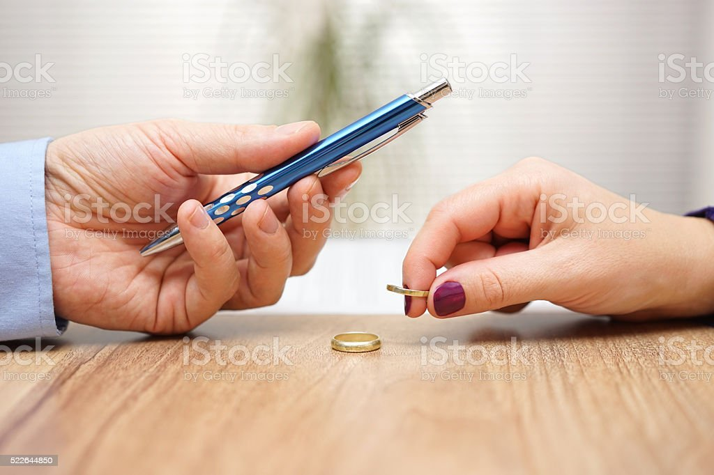 Husband is giving pen to sign divorce papers his wife stock photo