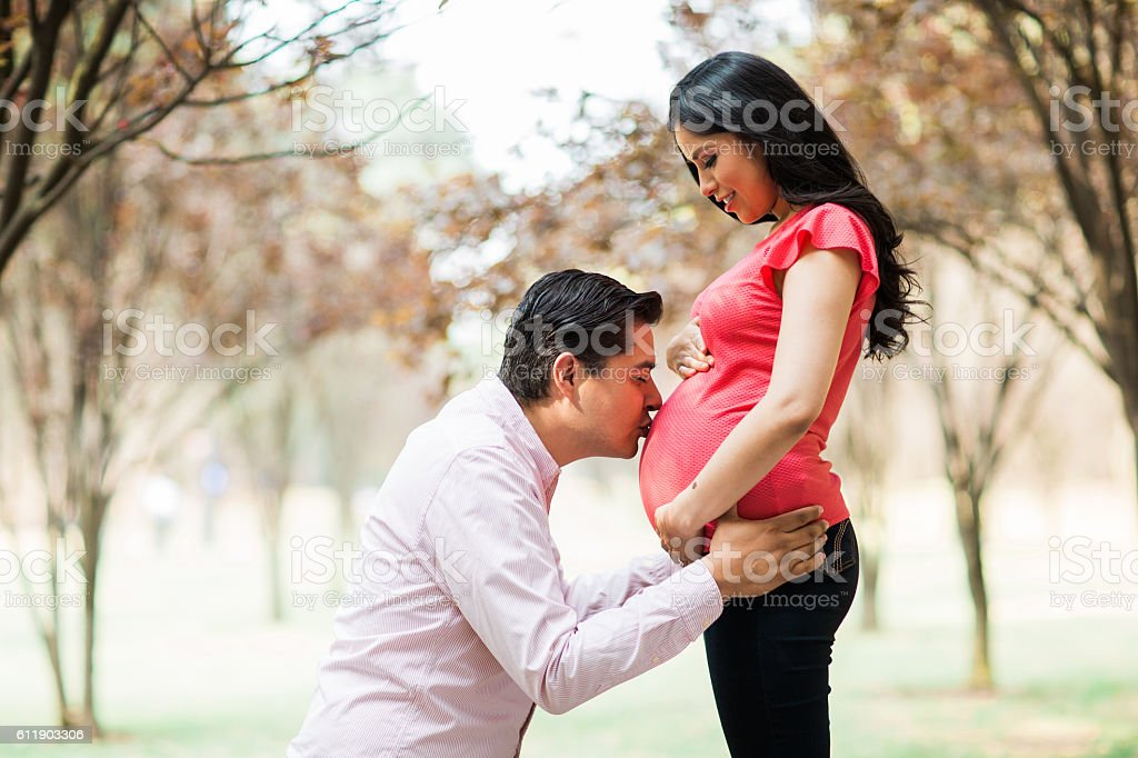 Husband kissing belly of pregnant wife stock photo