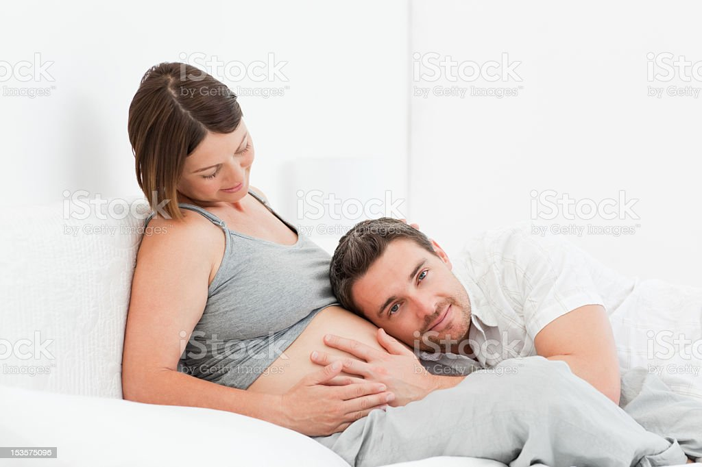 Husband listening to his wife's belly stock photo