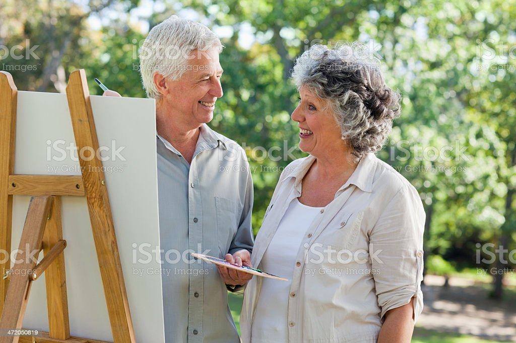 Husband painting on canvas smiles at wife royalty-free stock photo