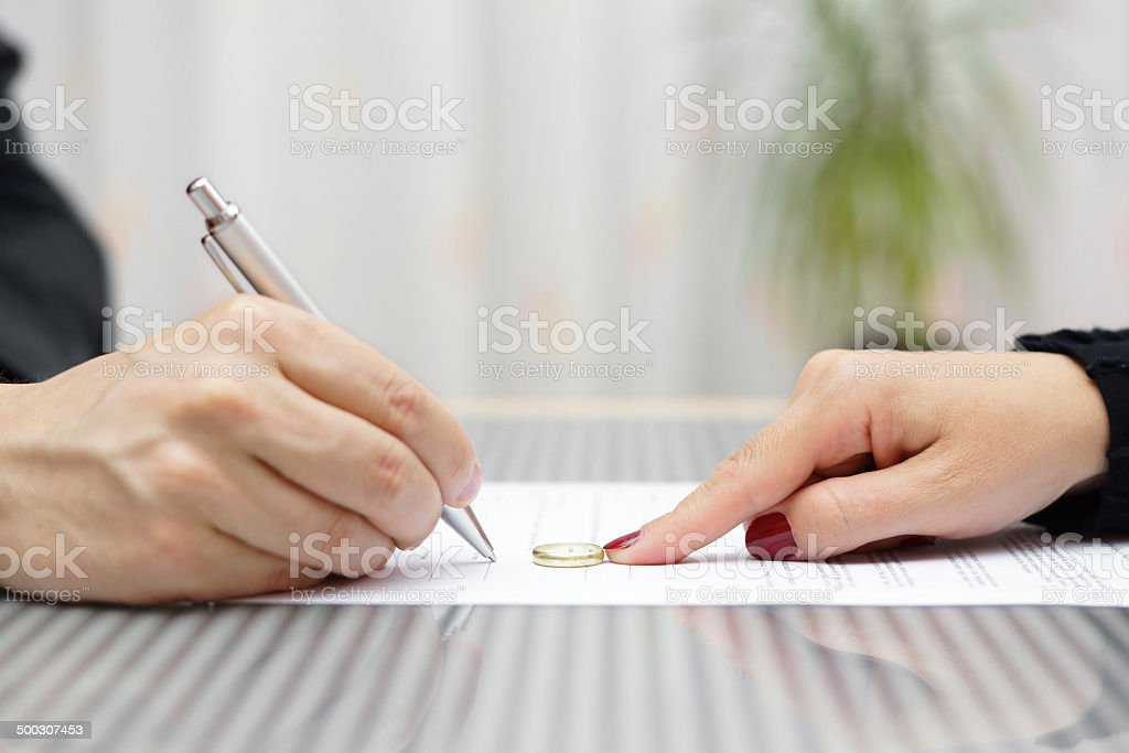 husband signing divorce agreement and woman push away weeding ring stock photo