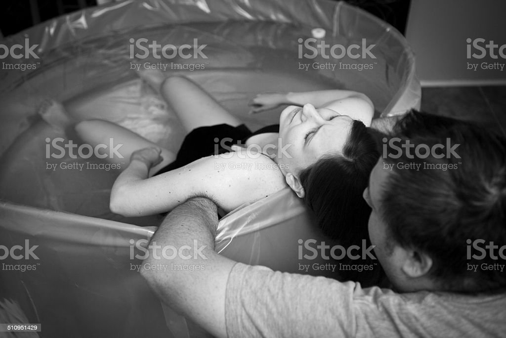 Husband Supporting Wife During Home Water Birth stock photo