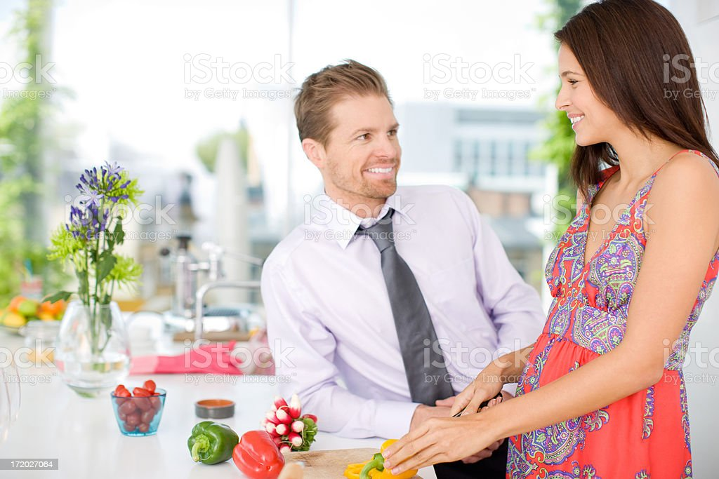 Husband talking to wife while she cuts vegetables in kitchen royalty-free stock photo