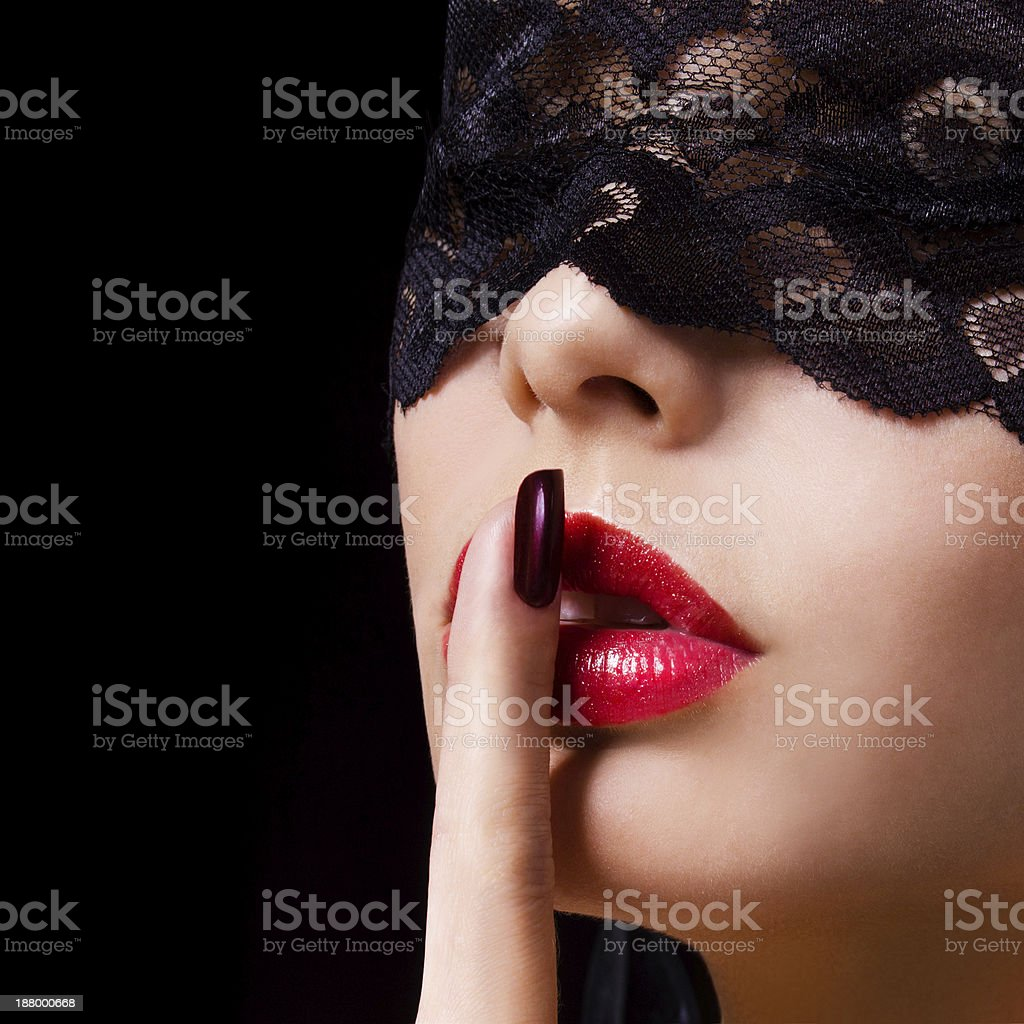 Hush. Sexy woman with lace mask over black stock photo