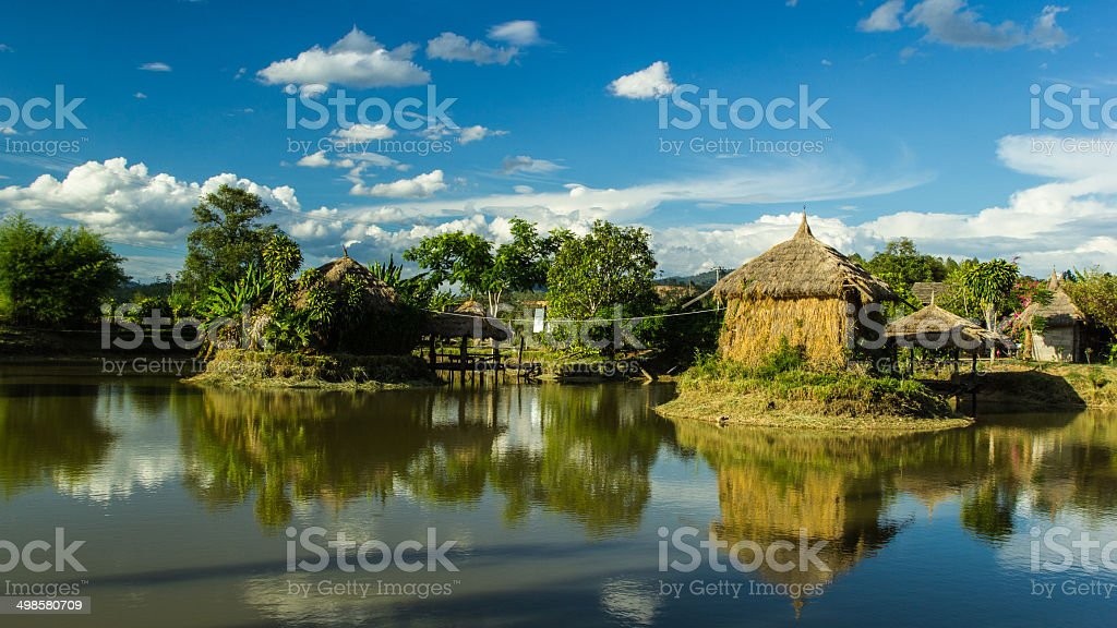 Hut made of straw over water. stock photo