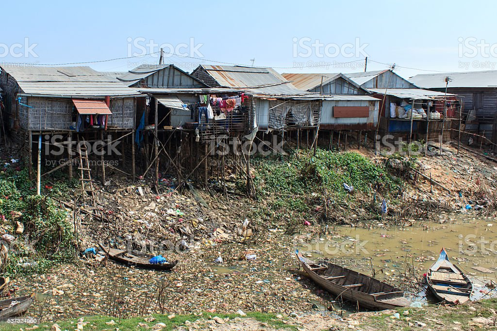 hut village - slum on polluted river in cambodia stock photo