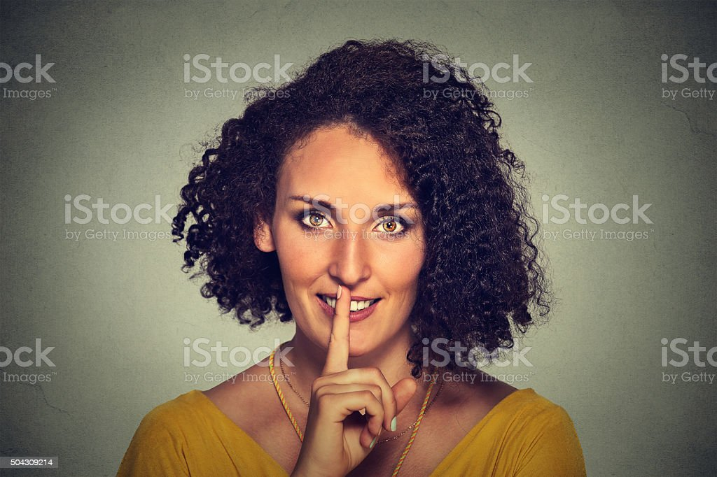 hwoman placing finger on lips asking shhh quiet silence stock photo