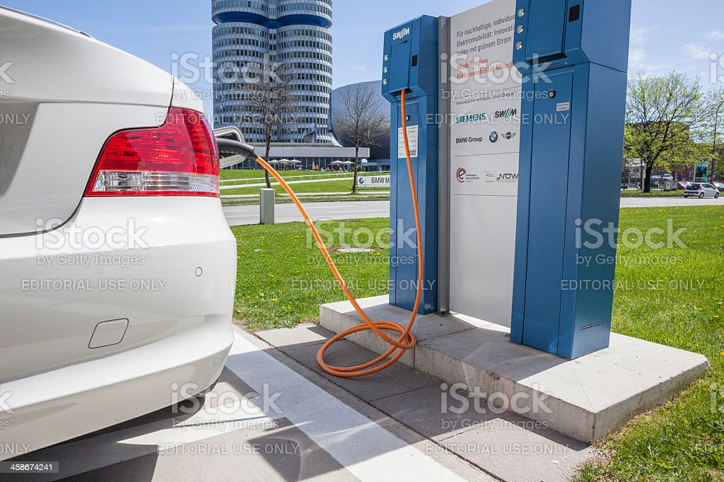 Hybrid car at electric charging station stock photo