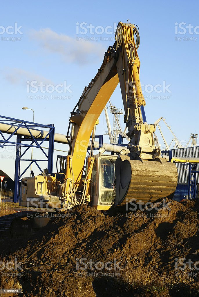 Hydraulic excavator at work. Shovel bucket against blue sky royalty-free stock photo
