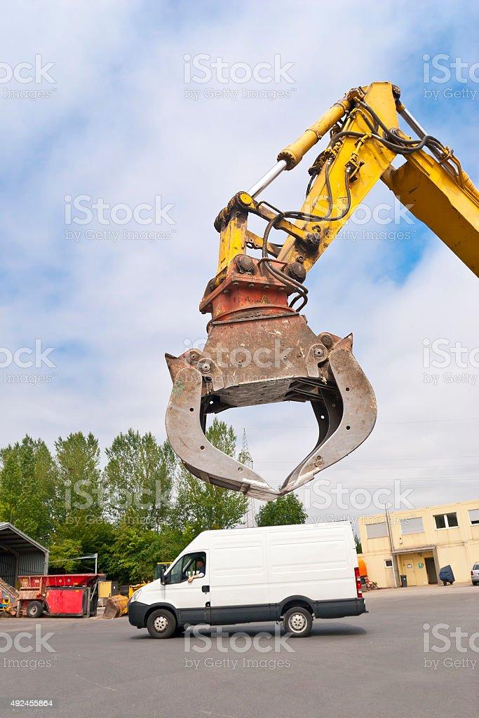 Hydraulic Gripper of an excavator over a cargo van stock photo
