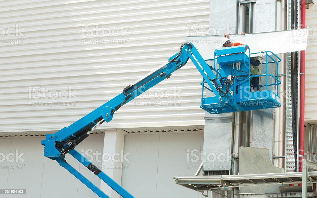 Hydraulic mobile construction platform elevated towards a blue stock photo