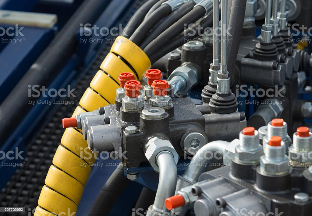 Hydraulic tubes, fittings and levers of lifting mechanism stock photo