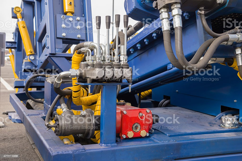Hydraulic tubes, fittings and levers on control panel of  mechan stock photo
