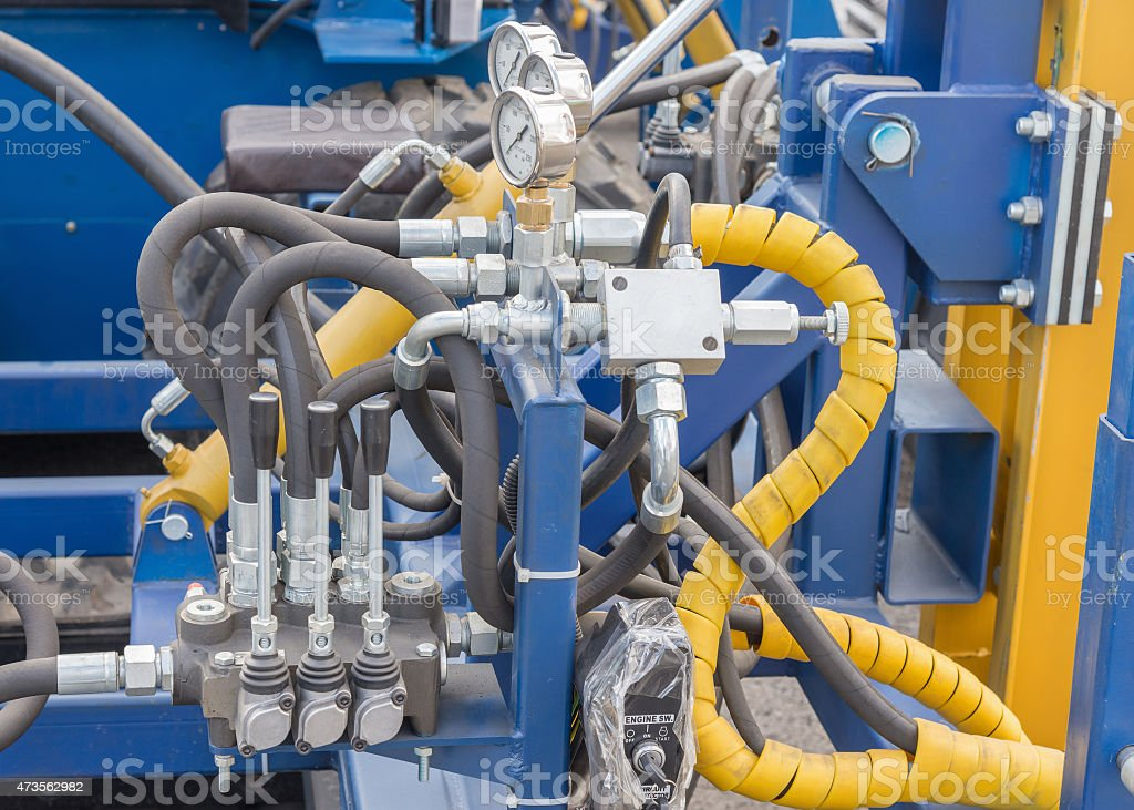 Hydraulic tubes, fittings and levers on control panel stock photo