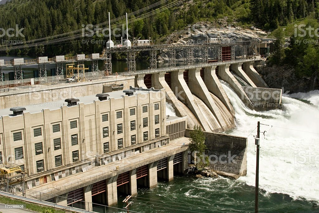 Hydro electric power plant in mountains with churning water stock photo