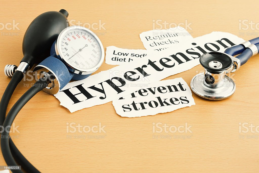 Hypertension headlines with stethoscope and blood pressure measuring device stock photo