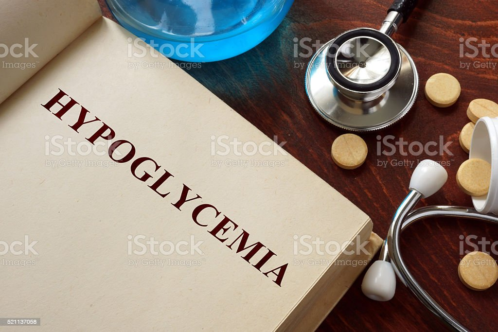 Hypoglycemia  written on book with tablets. stock photo