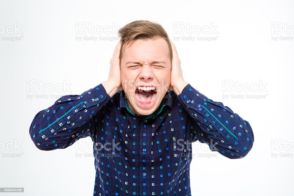 Hysterical mad young man closed ears with hands and screaming stock photo