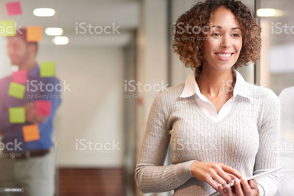 a modern female business woman stands waist up outside her...