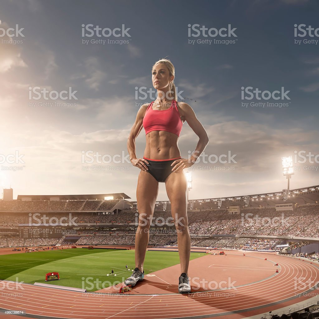 iant Woman Athlete Standing in Floodlit Athletics Stadium stock photo