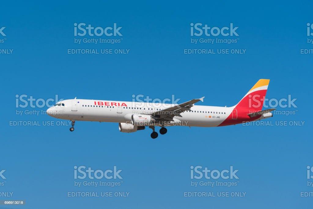 Iberia Airbus 321 is landing in Madrid Barajas airport. stock photo