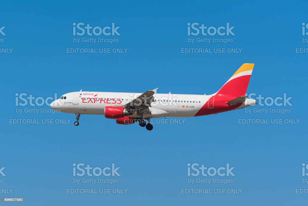 Iberia express Airbus 320 is landing in Madrid Barajas airport. stock photo