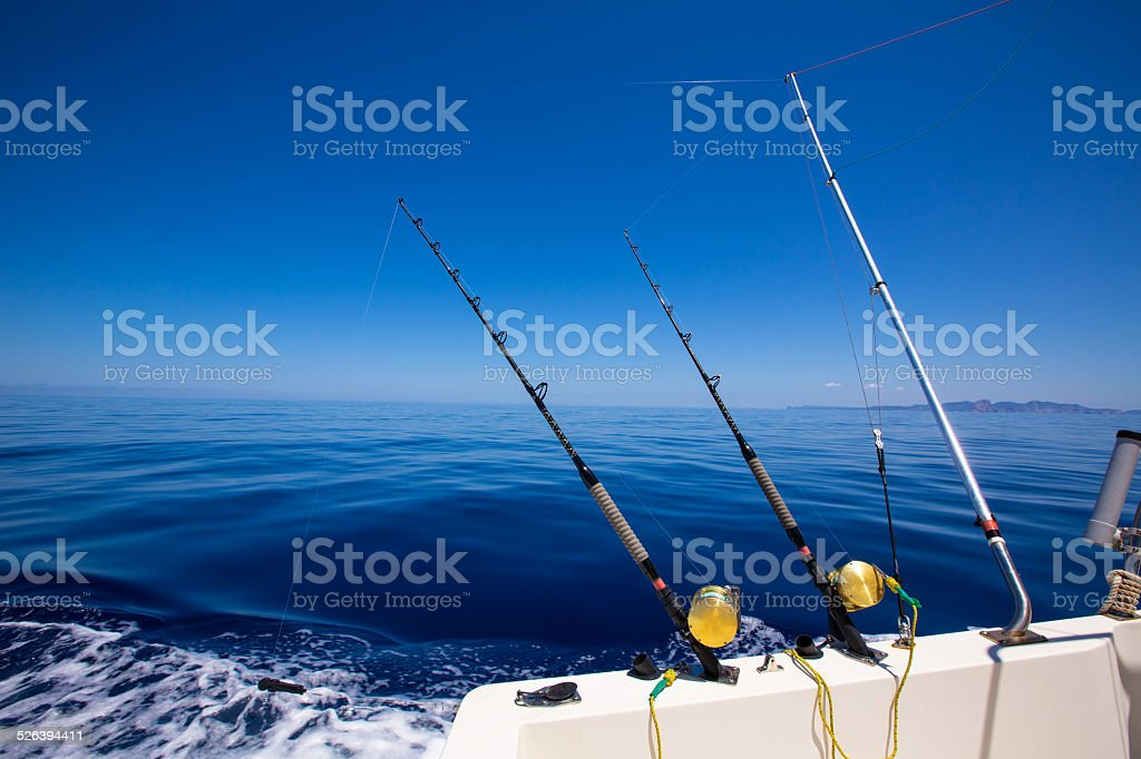 Ibiza fishing boat trolling rods and reels in blue sea stock photo