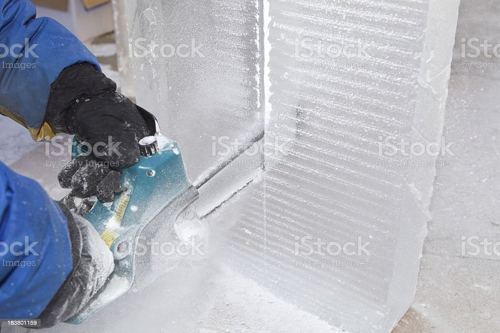 Ice Carver Using Chainsaw to Cut Block stock photo