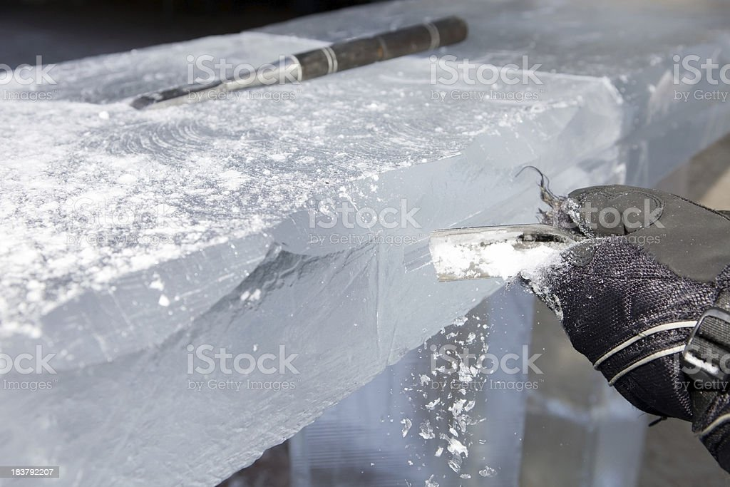 Ice Carver Using Chisel to Carve Decorative Bar stock photo