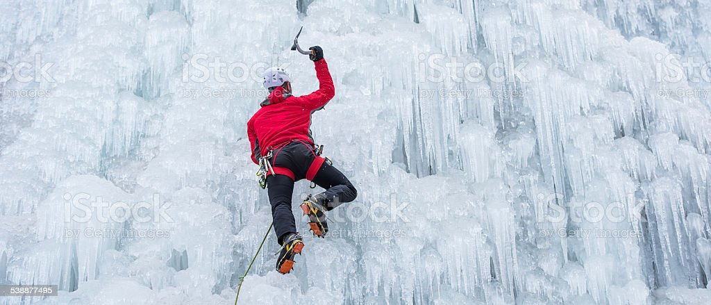 Ice Climber Ascending a Frozen Waterfall stock photo