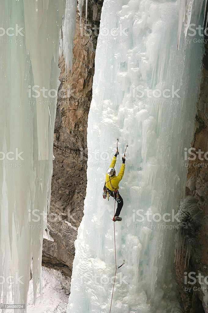 Ice Climber Extreme Adventurer on Steep Frozen Waterfall stock photo