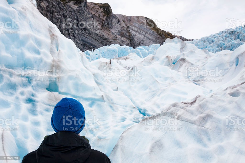 Ice climber looking at view Franz Josef Glacier, New Zealand stock photo