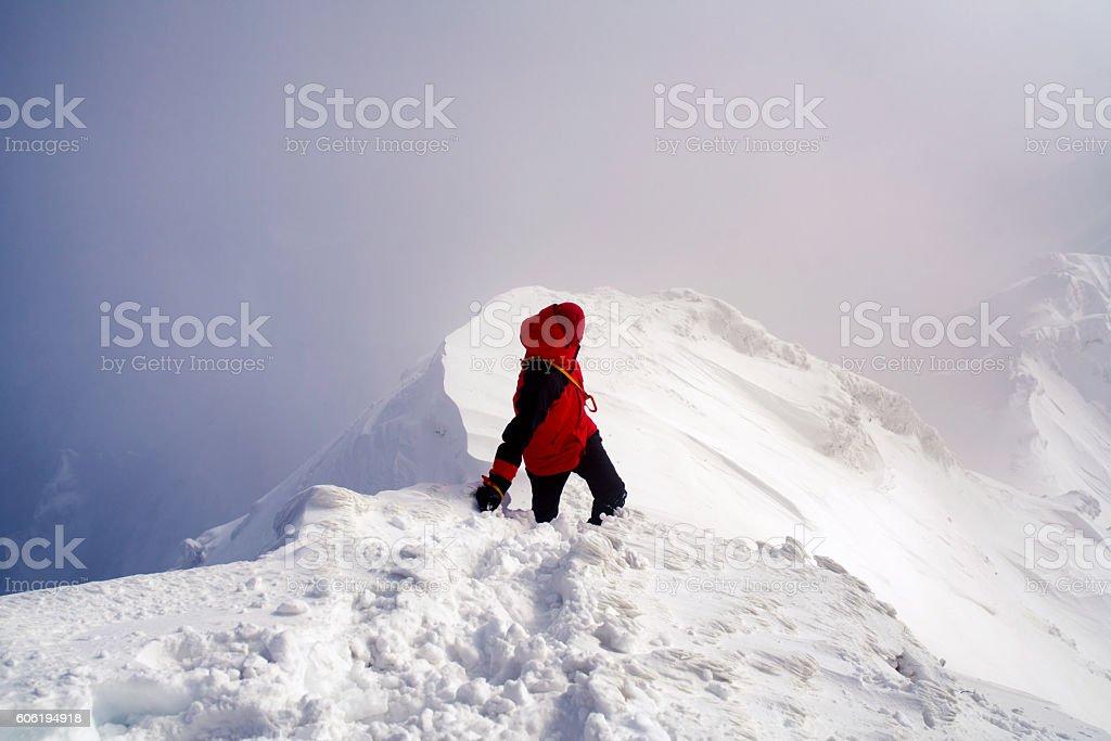 Ice climber looking back along a mountain ridge stock photo